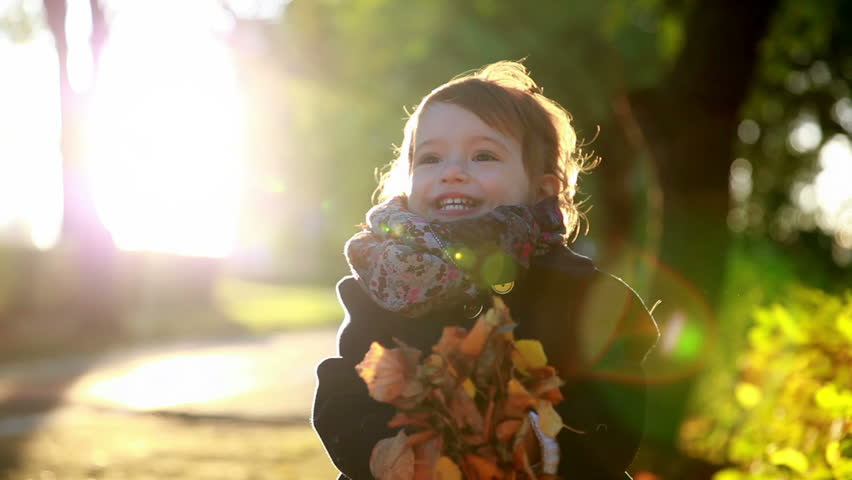 Kid throws yellow leaves in autumn park. | Shutterstock HD Video #7456087