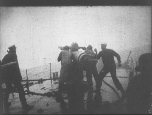World War I - 1914-1918 - Sailors load artillery cannon and fire upon German submarine as it submerges. - 4K stock video clip
