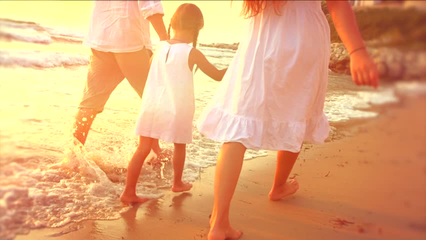 Happy family - father, mother and daughter having fun outdoors. Young joyful family with beautiful little girl in a white dress walking seashore along coastline. Slow motion 240 fps HD 1080p