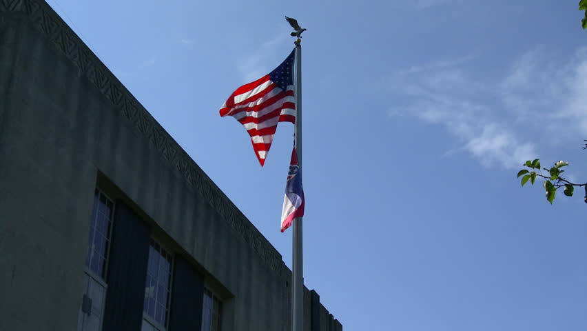 An American flag and Mississippi state flag fly high at the court house in downtown Vicksburg, Mississippi. The state flag is designed as a reminder of the history of rebellion of the American South. - HD stock footage clip