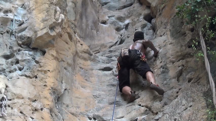 A rock climber adjusts the grip and footing while climbing up a rock formation, attaches a hook into the wall before climbing again, low angle, pan shot - HD stock footage clip