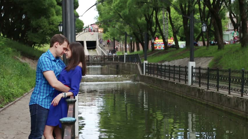 Man leans over woman and kisses her near small river in park at summer day
