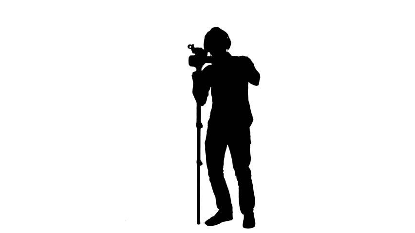 Cameraman monopod silhouette working - 1080p Silhouette of a cameraman with a monopod shooting video - Full HD | Shutterstock HD Video #7496659