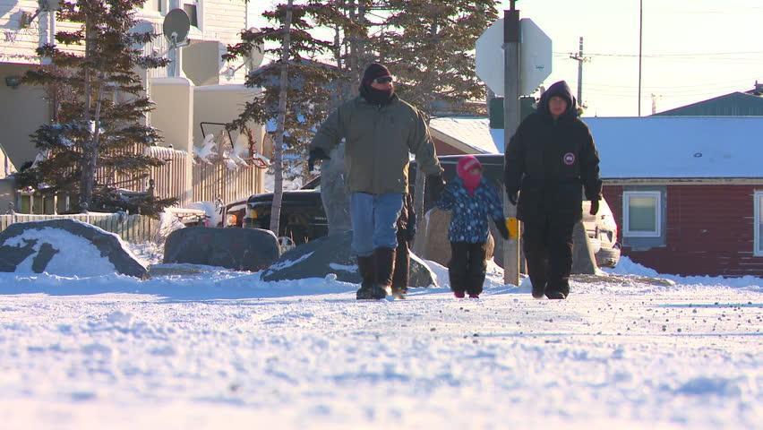 CHURCHILL, MANITOBA, CANADA - CIRCA 2014 - People walk along a snowy road at Churchill, Manitoba, Canada, Hudson Bay.