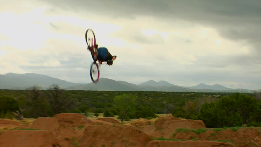 A mountain biker performs dirt jumps and tricks in a park | Shutterstock HD Video #7533811