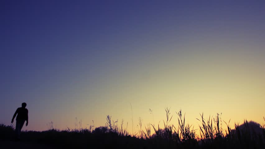 silhouette of man with rucksack walks uphill against sunset sky from camera