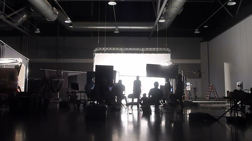 Unrecognizable film and photo crew working on professional studio shoot, time lapse.