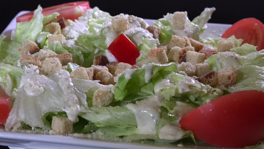 Beautiful caesar salad turning with dressing croutons and parmesan cheese
