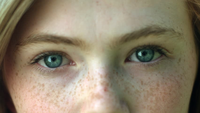 A CloseUp Of A Young Woman's Eyes, She Stares Into Camera, Then Her Eyes Brighten As She Smiles
