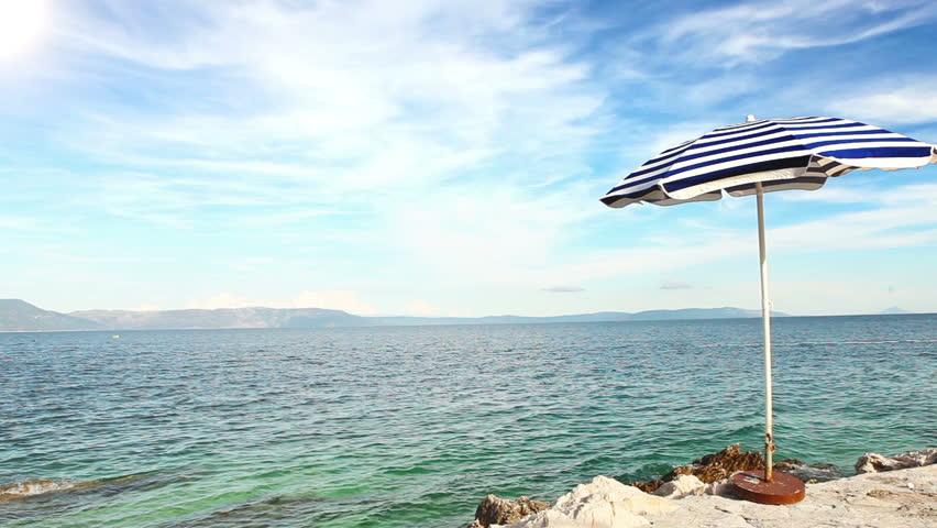 Alone beach retro style umbrella on the croatian shore - HD stock footage clip
