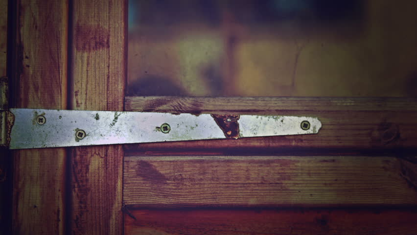Rustic door hinge HD stock footage. A close up dolly shot of an exterior door hinge fixed to a wooden shed door. #7637149