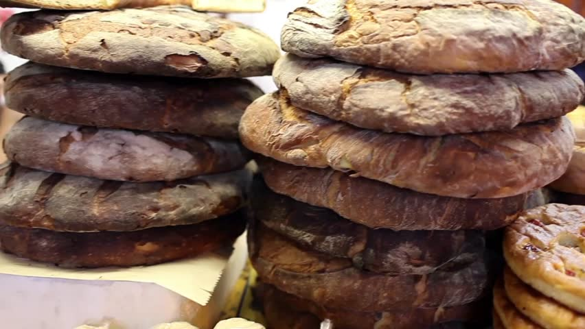 Video clip of different varieties of fresh baked Apulian bread for sale on a market stall.