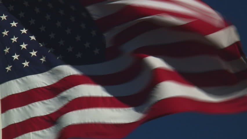 real United States of America flag flying flying against clear blue sky - HD, no audio, tight shot - HD stock footage clip