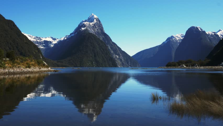Mitre peak reflected in the calm waters of new zealand's milford sound | Shutterstock HD Video #7661521