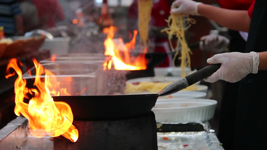 Professional Chef in a Commercial Kitchen Cooking Flambe Style. Chef frying food in flaming pan on gas hob in commercial kitchen.