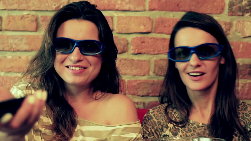 Women laughing while watching movie in 3d glasses and eating popcorn