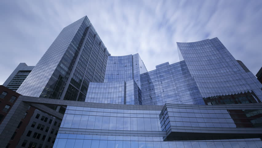 4K Time lapse of perspective view to steel blue glass skyscrapers with clouds passing by, business concept of successful modern architecture with long exposures - 4K stock footage clip