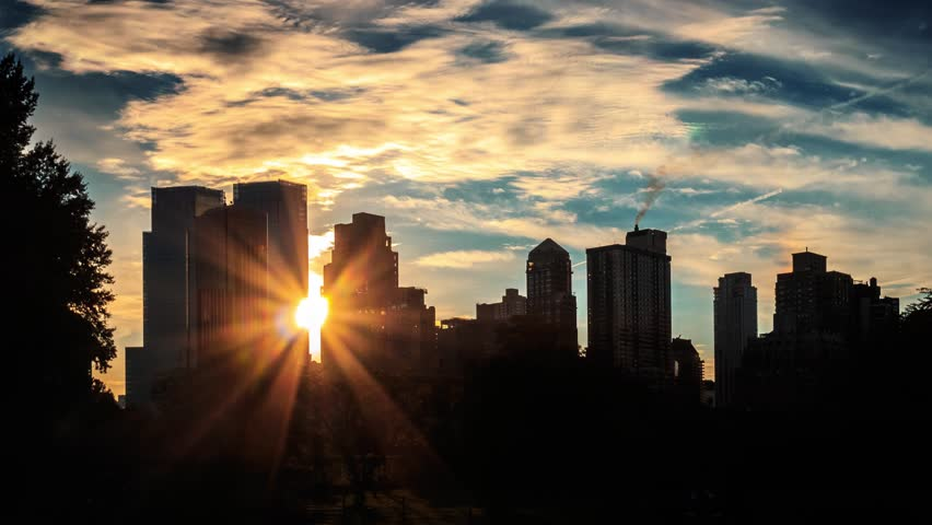 Sun setting behind buildings silhouettes. New York City skyline sunset timelapse. #7715872