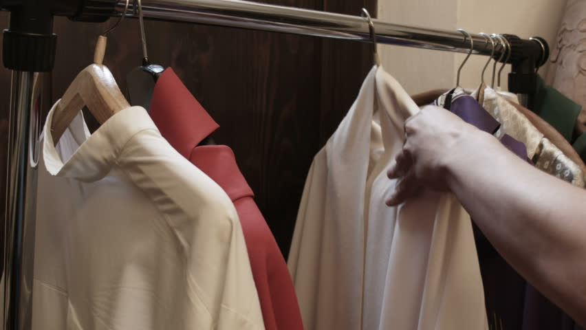 Young priest hand choosing the dress for the catholic holy mass - HD stock video clip