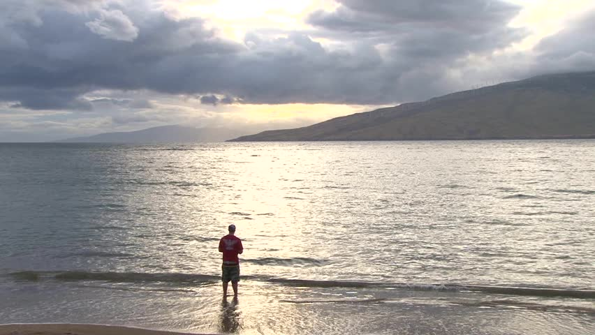 Person fishing from sandy shore in maui hawaii at sunset for Shore fishing maui