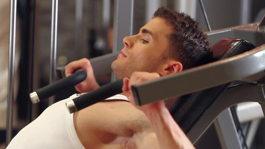 Handsome sporty man is exercising in gym centre - HD stock video clip