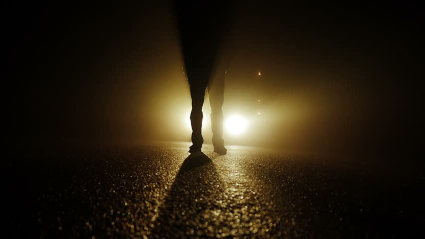 silhouette of person walking into dark night car lights