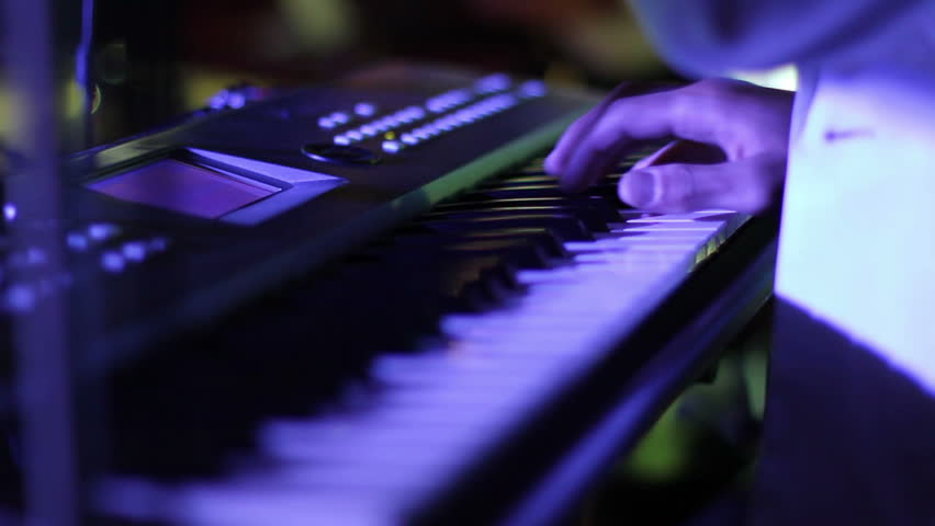 Musician playing on keyboards in disco lights - HD stock video clip