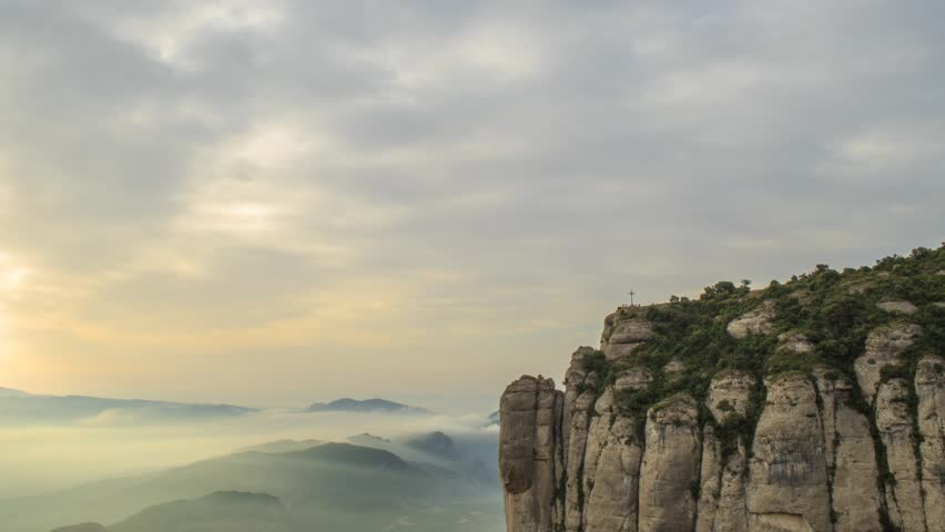 La Creu de Sant Michel / the Cross of Saint Michel at the monastery of Montserrat after sunrise with golden, rose colored clouds.  Near Barcelona in Catalonia, Spain. Timelapse footage.