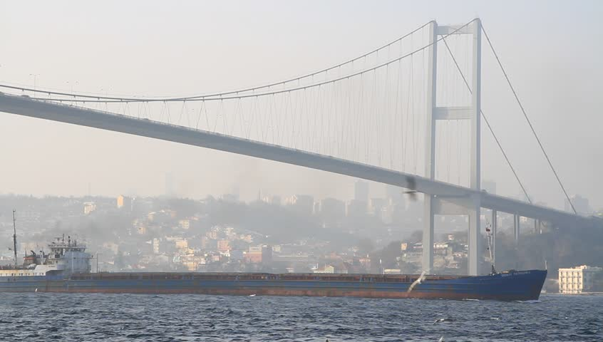 Air pollution in Istanbul. Smog with a cargo ship passing in Bosporus. Oil Products Tanker sailing under Bosphorus Bridge in Istanbul. Some 50,000 ships pass through the Straits every year.