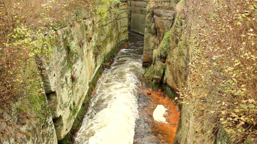 Fast full-flowing foamy water between sandstone rocks, orange sediments on dirty bank. Deep riverbed hewed into sandstone block - HD stock footage clip