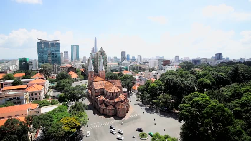 HO CHI MINH CITY, VIETNAM - NOV 01, 2014: Video view on Notre-Dame Cathedral( Nha Tho Duc Ba) in Ho Chi Minh City. Traffic with unrecognizable people can be seen in the foreground.