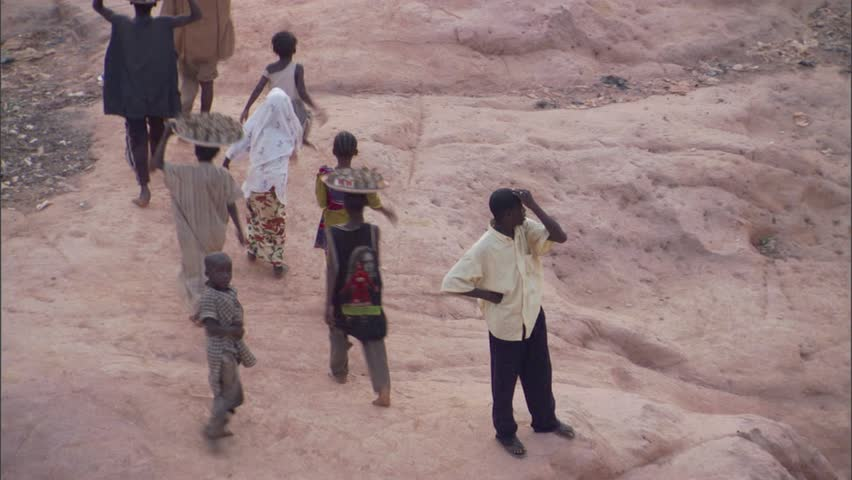 Villagers walking and carrying trays on their heads in Kano, Nigeria, - HD stock video clip