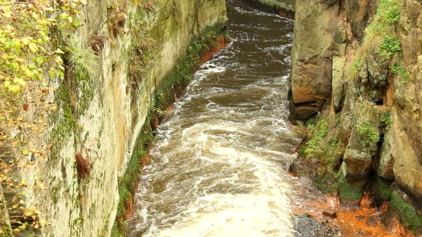 Fast full-flowing foamy water between sandstone rocks, orange sediments on dirty bank. Deep riverbed hewed into sandstone block - HD stock video clip