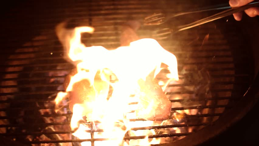 Steaks sizzle on flaming grill - HD stock footage clip