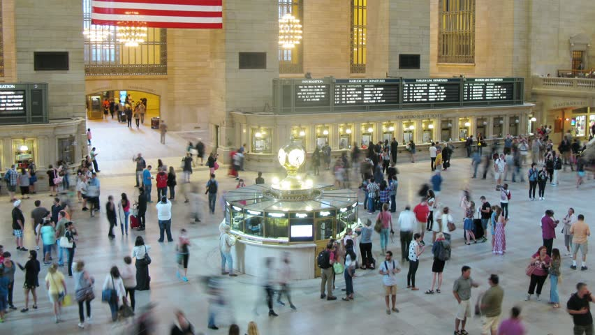 NEW YORK CITY - AUGUST 23, 2014 (Time lapse): People move at Grand Central Station, flag in the foreground. - HD stock video clip