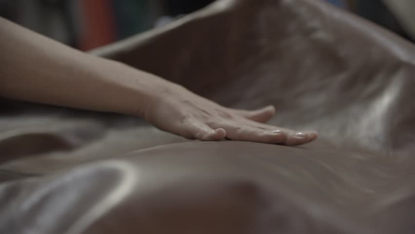 A woman feels the texture of leather with her hand rubbing in and out of focus. (slow motion)