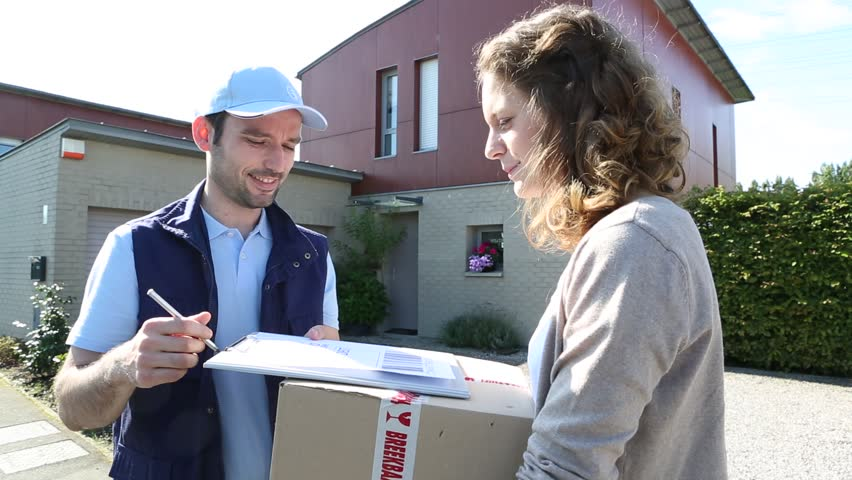 Young attractive woman signing on delivery paper