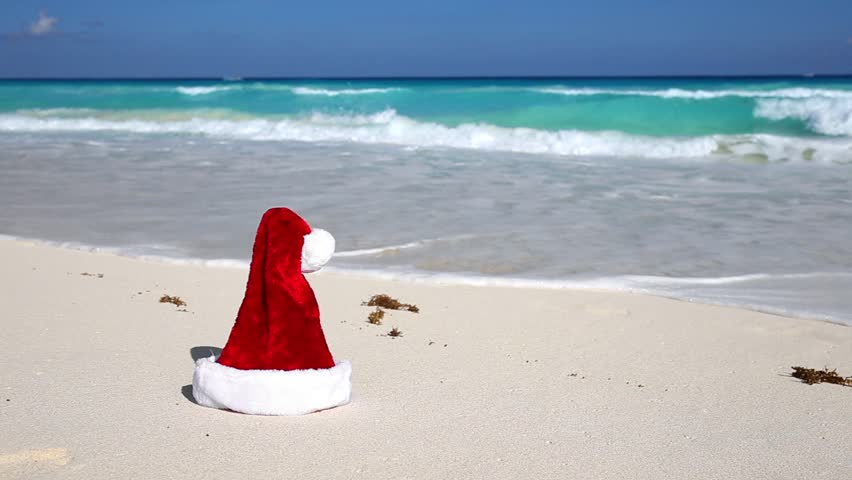 Santa Hat on white tropical sandy beach with Caribbean sea background