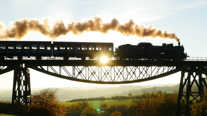 epic aerial view  steam engine train crossing bridge  sunset magic hour  locomotive
