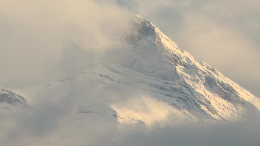 Time lapse clouds drift around and over winter mountain peak covered in snow. Three Sisters mountain group in the Canadian Rockies above the town of Canmore near Banff National Park, Canada