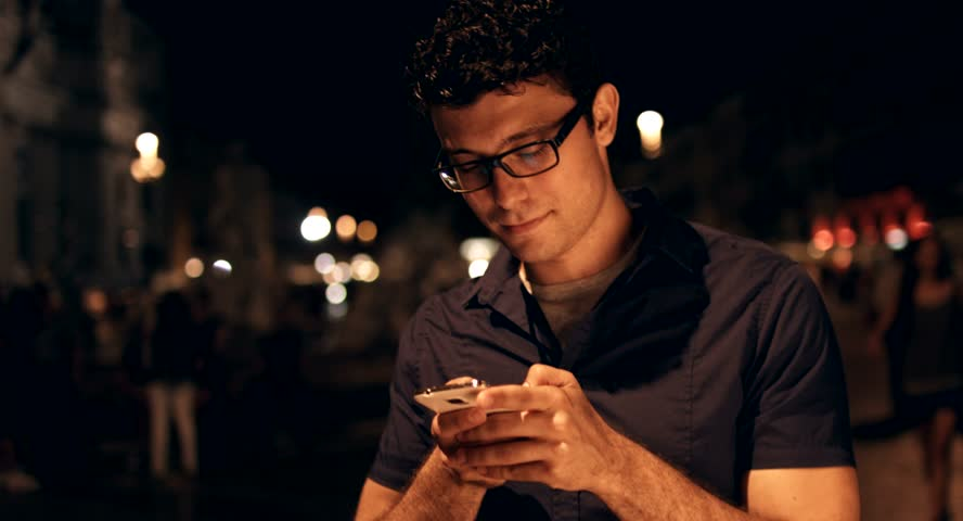 Handsome Young Businessman taping on Smartphone Night Vacation