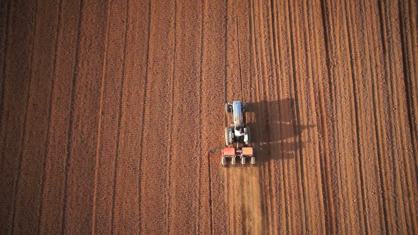 Aerial of tractor on harvest field (top view from height) - HD stock footage clip