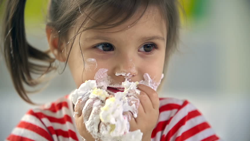 Close up of adorable little girl devouring cake with her hands