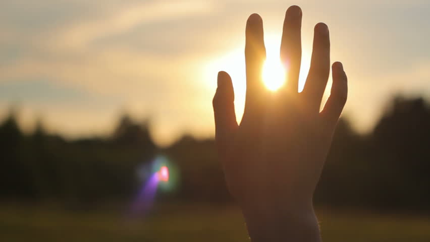 Close-up of raised hand in the sky against the sun in nature, religion, spirituality, camera movement - HD stock video clip