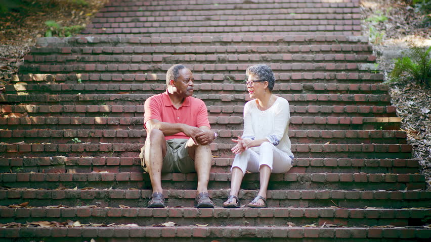 Mature Black Friends Talking While Sitting on Stairs in a Park - 4K stock video clip