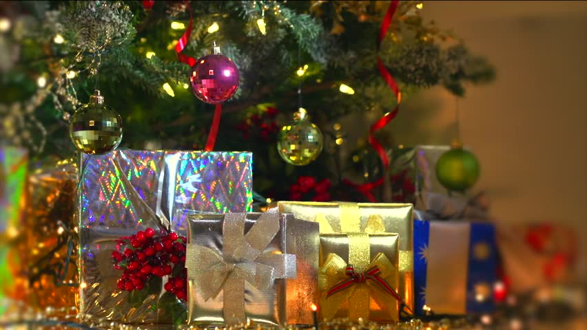 Placing a gift under the christmas tree stock footage