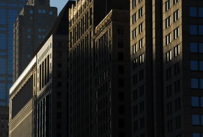 Sun rises on buildings in city time lapse
