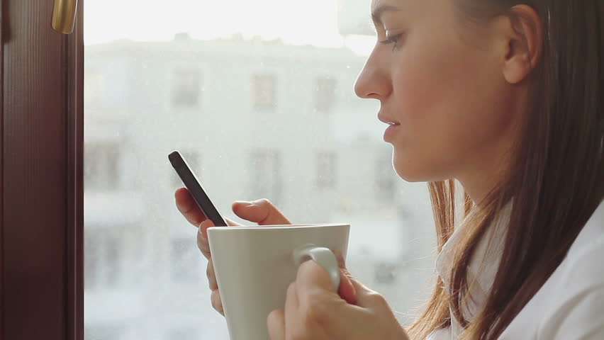 Young businesswoman drinking coffee and sending messages with her mobile phone