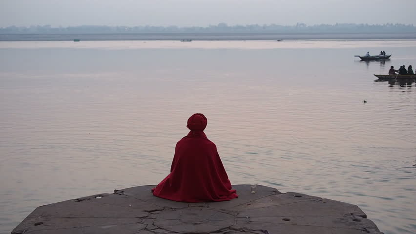VARANASI, INDIA - FEBRUARY 18, 2013: Sadhu (Indian holy man) sitting in meditation by the sacred Ganges river in Varanasi, Uttar Pradesh, India.