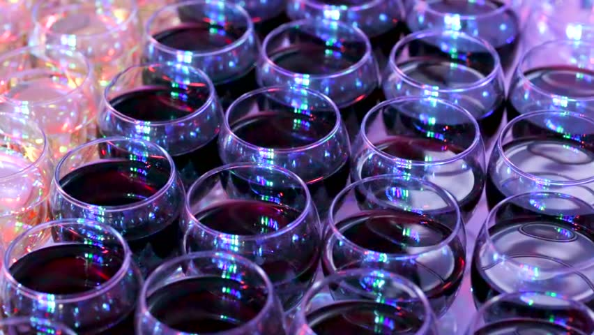Pan view of stemware with red and white wine lit by nightclub lights. - HD stock footage clip